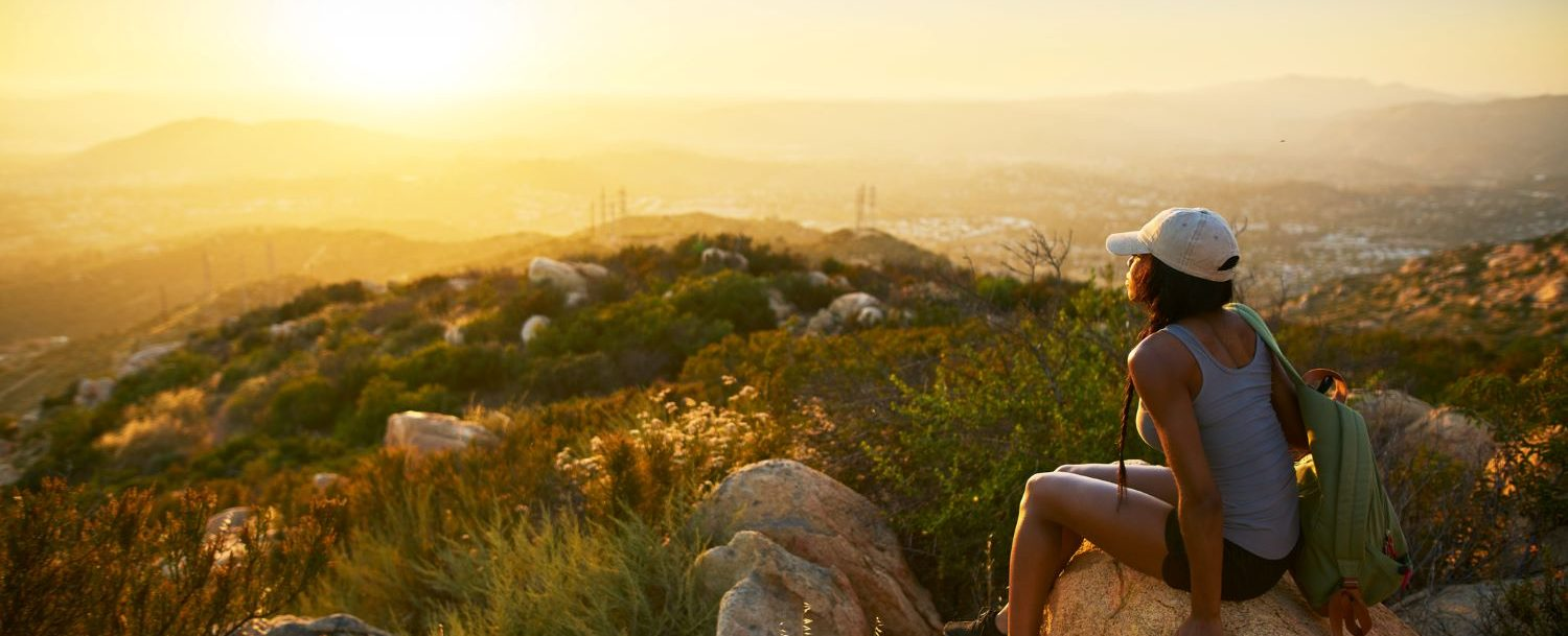 Hiker sitting on a rock that overlooks the city on one of the best hikes in San Diego
