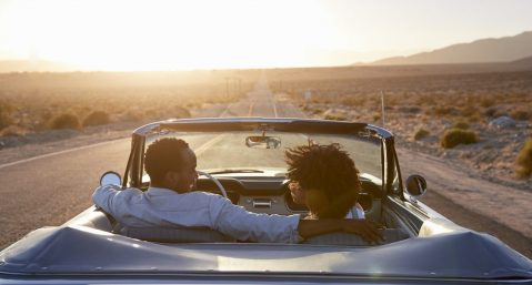 Couple in a convertible driving through the desert on their road trip from Phoenix/Scottsdale to San Diego